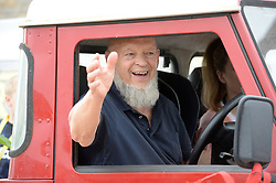 Michael Eavis celebrates a completed house in a housing development in Pilton village in Somerset.