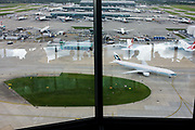 Aerial view (through control tower windows) showing expanse of airport land with airliners at London Heathrow. A panoramic view of the airfield and  parked and taxiing airliners. Consisting of five terminals on a site that covers 12.14 square kilometres (4.69 sq mi). London Heathrow is a major international airport, the busiest airport in the United Kingdom and the busiest airport in Europe by passenger traffic. It is also the third busiest airport in the world by total passenger traffic, handling more international passengers than any other airport around the globe.