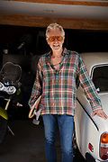 Smiling Senior Man In Garage With Car, Skateboard, And Motorcycle