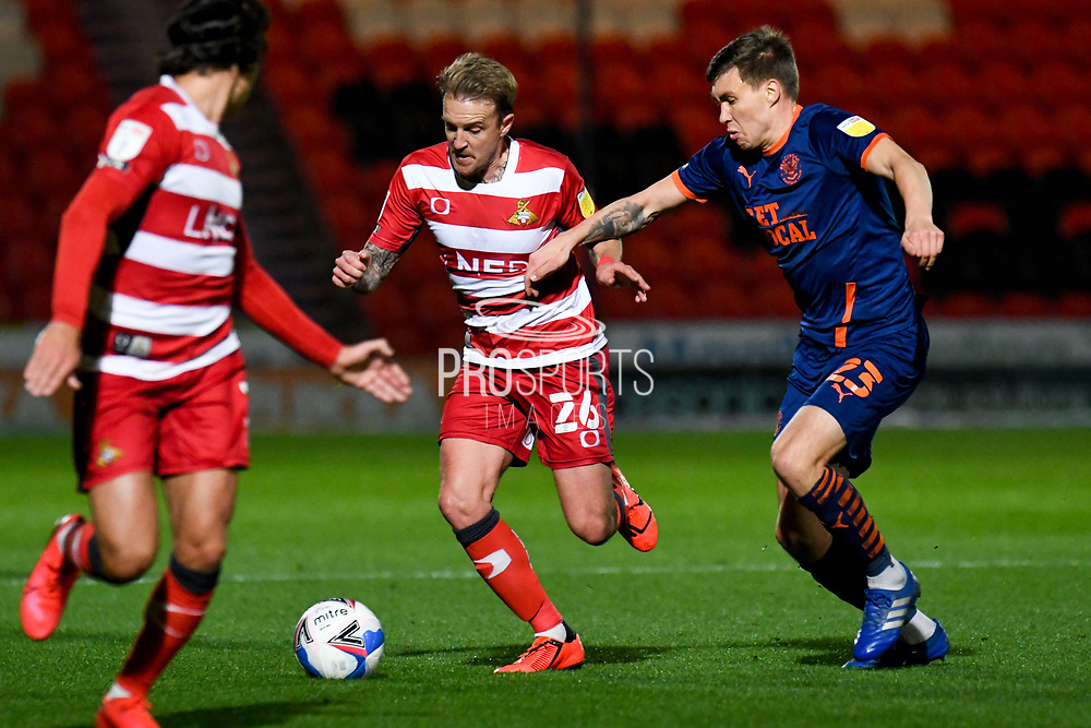 Doncaster Rovers midfielder James Coppinger (26) and Blackpool defender Daniel Leo Gretarsson (23) in action during the EFL Sky Bet League 1 match between Doncaster Rovers and Blackpool at the Keepmoat Stadium, Doncaster, England on 24 November 2020.