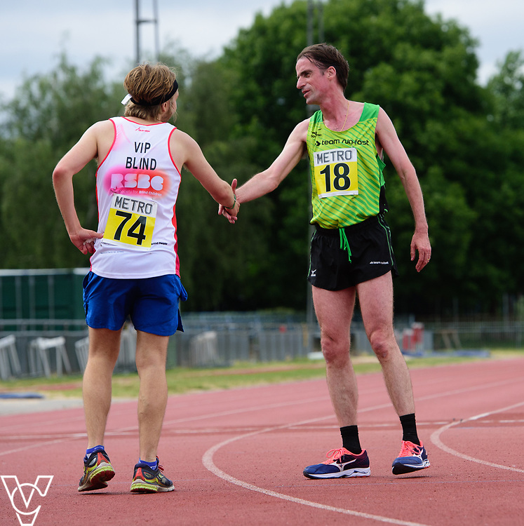 Event: 5000 meter relay<br /> Competitors, from left: Competitor #74 and Noel Thatcher<br /> <br /> Metro Blind Sport's 42nd Athletics Open, held at Mile End Stadium, Tower Hamlets, London.<br /> <br /> Picture: Chris Vaughan Photography for Metro Blind Sports<br /> Date: June 16, 2018