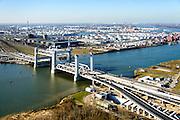 Nederland, Zuid-Holland, Rotterdam, 18-02-2015; bouw van de nieuwe Botlekbrug.<br /> De brug over de Oude Maas is een hefbrug, een van de twee brugdelen in geheven toestand. De heftorens van de oude brug gaan verscholen achter de nieuwe brug. Olietanks van Odfjell Terminals en Essoraffinaderij in de achtergrond. Ingang Botlektunnel in de voorgrond.<br /> Construction of the new Botlek bridge. The bridge over the Oude Maas is a vertical-lift bridge or lift bridge, one of the two bridge sections raised. <br /> luchtfoto (toeslag op standard tarieven);<br /> aerial photo (additional fee required);<br /> copyright foto/photo Siebe Swart