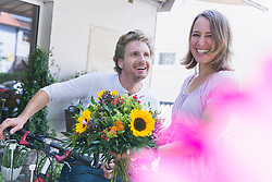 Mid adult couple in front of flower shop, smiling