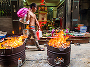 """10 AUGUST 2014 - BANGKOK, THAILAND:     A man walks by barrels burning joss paper and hell money in front of a home in a back alley in the Chinatown section of Bangkok. The seventh month of the Chinese Lunar calendar is called """"Ghost Month"""" during which ghosts and spirits, including those of the deceased ancestors, come out from the lower realm. It is common for Chinese people to make merit during the month by burning """"hell money"""" and presenting food to the ghosts.  PHOTO BY JACK KURTZ"""