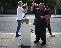 13 August 2017  : Premier League Football : Newcastle United v Tottenham Hotspur:  a matchday programme seller takes a swig of his drink : Photo: Mark Leech