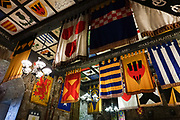 Banners & flags inside Comlongon Castle, a restored Medieval Scottish tower house dating from the late 1400s. Guests can stay in the attached Edwardian hotel, a baronial style mansion built 1900-02, set in 120 acres of manicured gardens, sweeping lawns, carp pond, lakes and woodlands, near Clarencefield and Dumfries, in southwest Scotland, United Kingdom, Europe. Originally built by the Murrays of Cockpool, Comlongon Castle remained in the Murray family until 1984. The castle is 50 feet square and stands 70 feet high, with walls over 4 meters thick, with impressive displays of weapons, armor and banners.