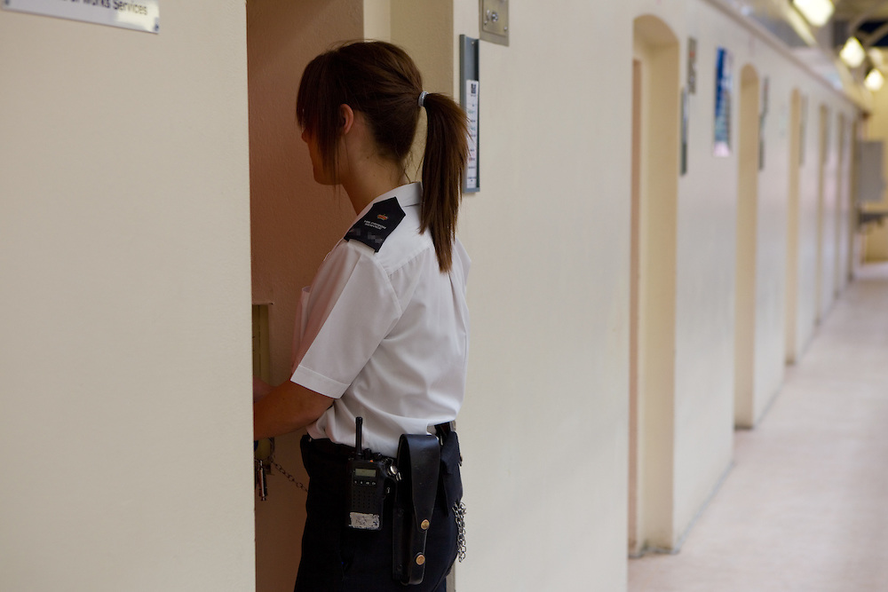 A young female prison officer checks the cells of each prisoner, making sure everything is in order. YOI Aylesbury.