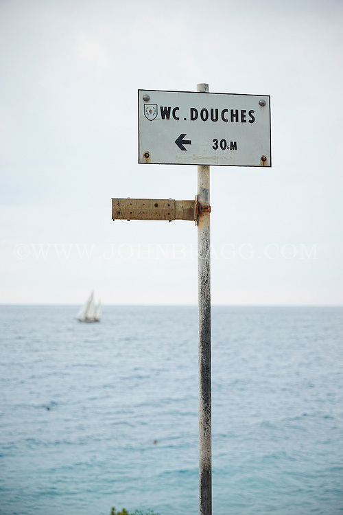 View from the Promenade des Anglais of a sign pointing towards Douches France, with the Mediterranean in the foreground, Nice France