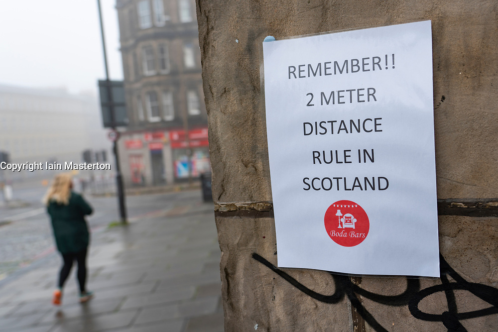 Edinburgh, Scotland, UK. 13 June 2020. On a foggy wet Saturday afternoon the streets of Edinburgh city centre remain very quiet and shops and businesses remain closed. Lockdown is expected to be relaxed next month.  Social distancing remains 2m in Scotland warning sign on pub wall. Iain Masterton/Alamy Live News