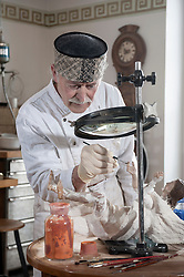 Senior sculptor colouring a Jesus Christ statue at workshop, Bavaria, Germany