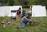 A member of the 124th New York State Volunteers cleans his weapon in the Union camp during a Civil War reenactment at the Orange County Farmers Museum on Sept. 23, 2006. Other military and civilian reenactors dressed in period uniforms and clothing are also in the camp.