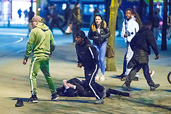 © Licensed to London News Pictures . 07/04/2017 . Manchester , UK . 10th in a sequence . Five youths on one as a fight breaks out in which a man's head is kicked and stamped upon , in Piccadilly Gardens . Greater Manchester Police have authorised dispersal powers and say they will ban people from the city centre for 48 hours , this evening (7th April 2017) , in order to tackle alcohol and spice abuse . Photo credit : Joel Goodman/LNP