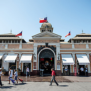 The main entrance to Mercado Central de Santiago, Chile's central market. The market specializes in seafood, a staple food category of Chilean cuisine. The building is topped with an ornate cast-iron roof.