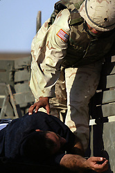 A U.S. soldier accompanies a person injured at the UN base inside the Canal Hotel where a cement truck packed with explosives detonated outside the offices killing 20 people and devastating the facility in Baghdad, Iraq on Aug. 19, 2003. This was an unprecedented suicide attack against the world body with at least 100 people wounded.