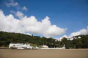"""Portmeirion, in North Wales, is a resort, where no one has ever lived. A self-taught Welsh architect named Sir Clough Williams-Ellis built it out of architectural salvage between the 1920s and 1970s, loosely based on his memories of trips to Portofino. Including a pagoda-shaped Chinoiserie gazebo, some Gothic obelisks, eucalyptus groves, a crenellated castle, a Mediterranean bell tower, a Jacobean town hall, and an Art Deco cylindrical watchtower. He kept improving Portmeirion until his death in 1978, age 94. It faces an estuary where at low tide one can walk across the sands and look out to sea. At high tide, the sea is lapping onto the shores. Every building in the village is either a shop, restaurant, hotel or self-catering accomodation. The village is booked out at high season, with numerous wedding receptions at the weekends. Very popular amongst the English and Welsh holidaymakers. Many who return to the same abode season after season. Hundreds of tourists visit every day, walking around the ornamental gardens, cobblestone paths, and shopping, eating ice-creams, or walking along the woodland and coastal paths, amongst a colourful assortment of hydrangea, rhododendrons, tree ferns and redwoods. The resort boasts two high class hotels, a la carte menus, a swimming pool, a lifesize concrete boat, topiary, pools and wishing wells. The creator describes the resort as """"a home for fallen buildings,"""" and its ragged skyline and playful narrow passageways which were meant to provide """"more fun for more people."""" It does just that.///Portmeirion Hotel overlooking the estuary Afon Dwyryd towards Porthmadog and Tremadog. View from estuary. Portmeirion village up on hill."""