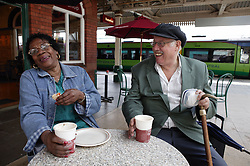 Elderly couple laughing in a cafe at train station,