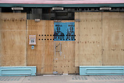 Boarded up shop front with blue posters of Arnold Schwartzenegger as The Terminator, using a take on his famous catch-phrase Well be back as the national coronavirus lockdown three continues on 3rd March 2021 in London, United Kingdom. With the roadmap for coming out of the lockdown has been laid out, this nationwide lockdown continues to advise all citizens to follow the message to stay at home, protect the NHS and save lives.