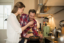 Young woman tasting food to her husband in kitchen, Munich, Bavaria, Germany