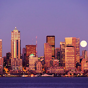 Twilight view of downtown Seattle, Washington across Elliot Bay from West Seattle with moonrise