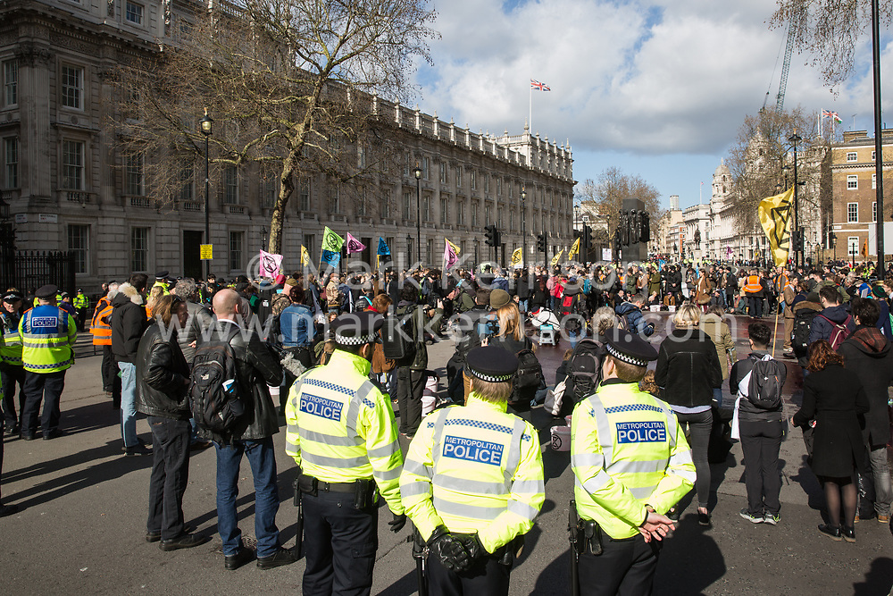 London, UK. 9th March, 2019. Climate activists from Extinction Rebellion gather in Whitehall after pouring artificial blood on the ground outside Downing Street as part of an act of civil disobedience named 'The Blood of Our Children' to call on the Government to take immediate steps to combat the current climate and ecological emergency.