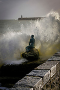 A large wave crashed over Cornelia Parker's Mermaid statue on Sunny Sands Beach, Folkestone, Kent, UK.  The Folkestone Harbour Arm and lighthouse can be seen in the horizon.  (photo by Andrew Aitchison / In pictures via Getty Images)