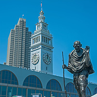 A bronze sculpture of Mohandas Gandhi stands amid crowds and vendor stalls at a Saturday farmer's market at the Embarcadero in downtown San Francisco.