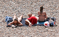 © Licensed to London News Pictures. 16/07/2014. Brighton, UK. People relaxing and sunbathing on Brighton beach at lunchtime. Temperatures in parts of the south east are expected to hit 30 degrees this week. Photo credit : Hugo Michiels/LNP