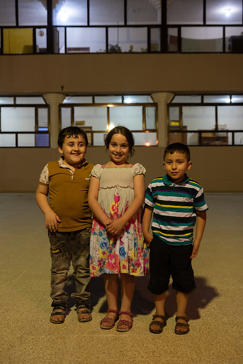 Three children stand in the courtyard at St. John the Baptist church (Ancient Church of the East) in Kirkuk, Iraq. (May 21, 2017)