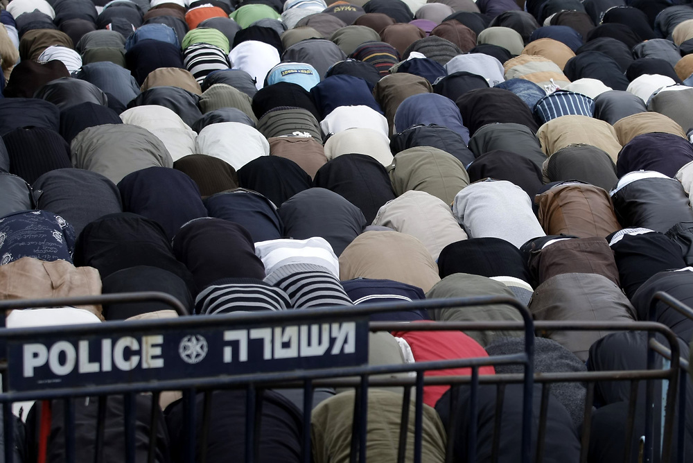 Palestinian Muslim worshippers perform the Friday prayers on the street, after they were denied entry to the Al Aqsa Mosque for security reasons, near east Jerusalem's Old City, on January 23, 2009. Israeli police restricted access to the Al-Aqsa mosque compound in Jerusalem to Palestinian men over 40 who had come to attend the first Friday sermon since a ceasefire halted the violence in the Gaza Strip.