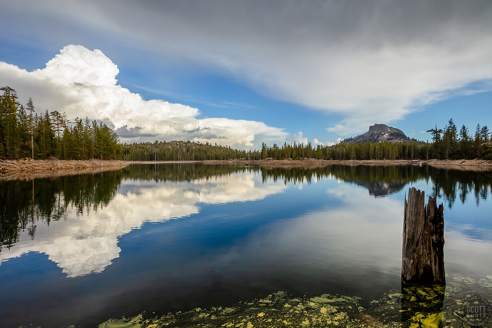 """""""Clouds at Cascade Lakes 2"""" - Photograph of a stump and cumulus clouds reflecting on the surface of Cascade Lakes with Devils Peak in the background."""