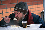 Moscow, Russia, 18/01/2006..Homeless men are fed in the street  outside a disinfection centre for the homeless. A Siberian weather front has brought temperatures down to minus 36C in the Russian capital and led to power cuts in the city.