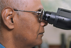 Biomedical scientist using a microscope to examine blood cell morphology,