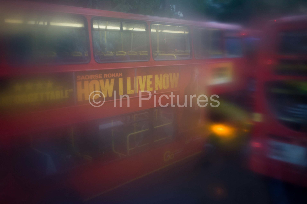 Seen through upper-deck window condensation, buses and traffic during damp, gloomy weather in central London. Low visibility and rain streaks obscures a clear view through the glass from the top level of this bus during its journey south through the London borough of Lambeth.