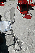 red and grey transparent chairs reflection on a outdoor public cafe terrace