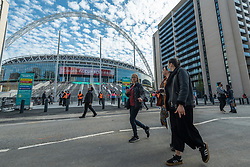 © Licensed to London News Pictures. 18/04/2021. LONDON, UK. Locals pass security guards on the new steps outside Wembley Stadium ahead of the FA Cup semi-final match between Leicester City and Southampton.   4,000 local residents have been invited to attend the match, the largest number of spectators attending a match in a UK stadium for over a year.  Covid-19 testing will take before and after the match and data gathered will be used to plan how all sports tournaments can escape lockdown.  Photo credit: Stephen Chung/LNP