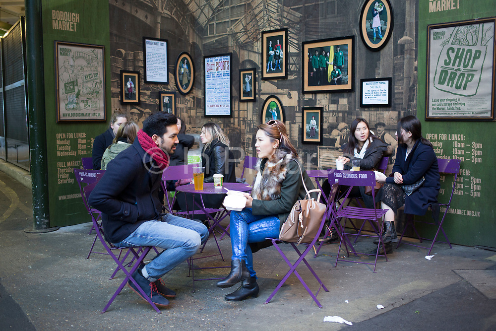 Asian visitors to Borough Market sit down for a coffee in a seated area. Borough Market is a wholesale and retail food market in Southwark, Central London, UK. It is one of the largest and oldest food markets in London, and a very popular weekend destination.