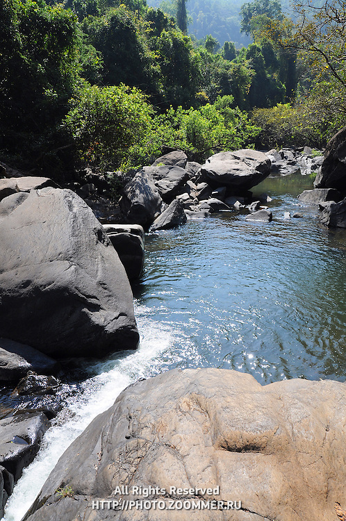 Lake and waterfall in mountains among huge stones and jungle forest