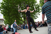 Street performer thrills the crowd with his knife act whilst balancing on a rope slack line being held up by members of the audience. Covent Garden plaza in the West End of London. The South Bank is a significant arts and entertainment district, and home to an endless list of activities for Londoners, visitors and tourists alike.