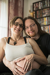 Portrait of pregnant couple with hands in heart shape on belly