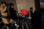 A mother and father carry their child's pushchair down steep steps in London.