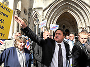 CENTRAL LONDON. Nick Griffin asks a supporter to move a flag out of his way. Nick Griffin leader of The British National Party outside the Royal Courts of Justice today after his case was adjourned.. 07 SEPT 2010. STEPHEN SIMPSON ..