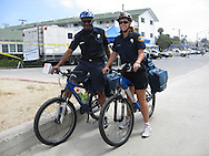 USA: California: San Diego County: San Diego: Paramedics patrol on bicycles along the beach boardwalk in the San Diego communities of Mission Beach and Pacific Beach.