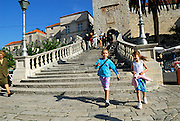 Two children (9 years old, 5 years old) at the base of the steps leading to the Revelin Tower and land gate (Kopnena Vrata) entrance into the old town of Korcula. Korcula old town, island of Korcula, Croatia.