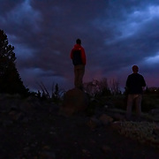 A couple friends enjoy the quiet beauty of a thunderstorm at Minaret Vista as night falls on Mammoth.
