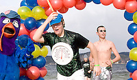 Tim Quinney followed by Kyle Perrault, members of the Interlakes Class of 2010 team, may need to adjust their thermometer by about  -25 degrees to correctly display the temperatures at Weirs Beach on Saturday for the 4th annual Turkey Plunge sponsored by the Salvation Army Laconia Corps.  (Karen Bobotas/for the Laconia Daily Sun)