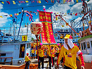 """02 JUNE 2017 - SAMUT SAKHON, THAILAND:  Participants in the parade for the City Pillar Shrine get off a boat that carried them up the Tha Chin River during the procession for the City Pillar Shrine. The Chaopho Lak Mueang Procession (City Pillar Shrine Procession) is a religious festival that takes place in June in front of city hall in Samut Sakhon. The """"Chaopho Lak Mueang"""" is  placed on a fishing boat and taken across the Tha Chin River from Talat Maha Chai to Tha Chalom in the area of Wat Suwannaram and then paraded through the community before returning to the temple in Samut Sakhon. Samut Sakhon is always known by its historic name of Mahachai.     PHOTO BY JACK KURTZ"""