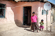 A woman with her daughter in front of their house in the Roma area of Frumusani.