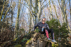 Fit young man relaxing on tree stump in forest
