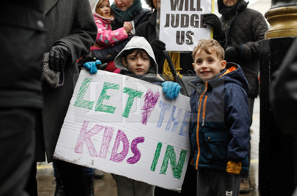 © Licensed to London News Pictures. 11/02/2017. London, UK. Young children hold up a pro refugee sign as they arrive with Lord Dubs 10 Downing Street in London to hand in a petition petition calling on the PM to reconsider lone child refugee policy.. Photo credit: Tolga Akmen/LNP
