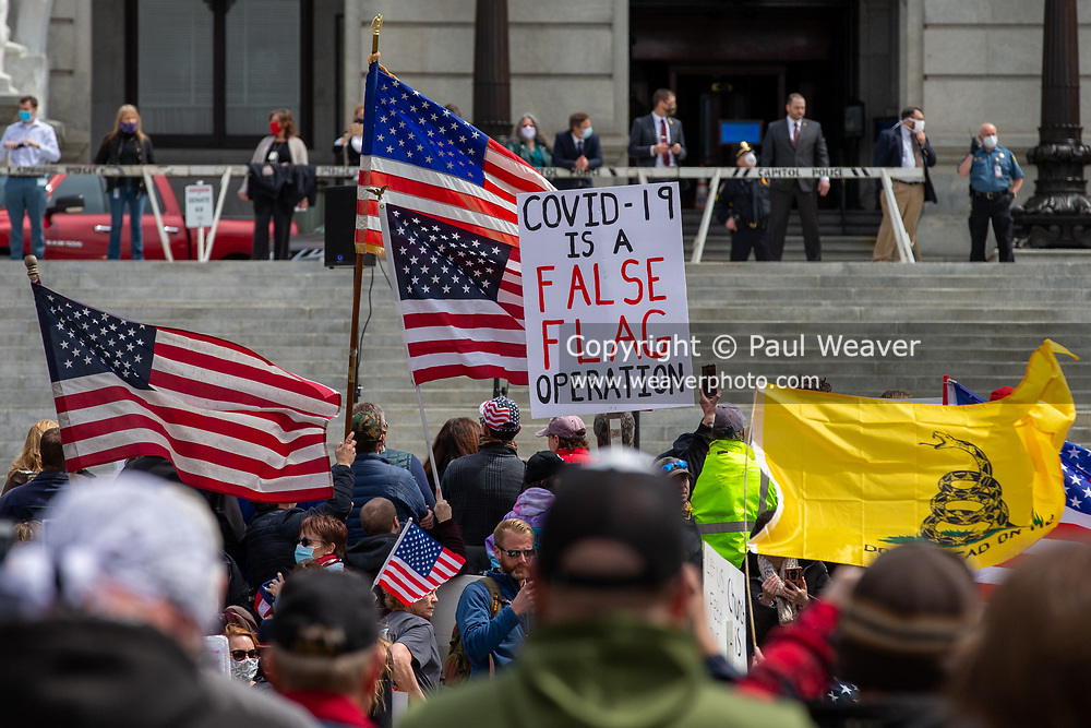 """A sign reading """"COVID-19 is a false flag operation"""" is during a ReOpen PA rally in Harrisburg, Pennsylvania on April 20, 2020. Protesters gathered at the Pennsylvania Capitol to demand that Governor Tom Wolf reopen the state's economy. (Photo by Paul Weaver)"""
